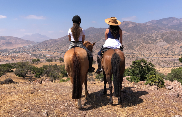 Two Women Riding Horses and facing the mountains in the Andes, Chile.